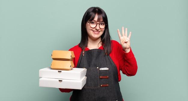 Plus la taille jolie femme souriante et à la recherche amicale, montrant le numéro quatre ou quatrième avec la main en avant, compte à rebours