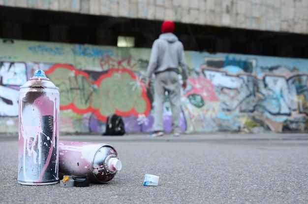 Plusieurs aérosols usés avec de la peinture rose et blanche se trouvent sur l'asphalte