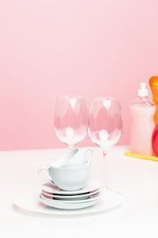 Plusieurs assiettes, une éponges de cuisine et une bouteille en plastique avec du savon liquide vaisselle naturel