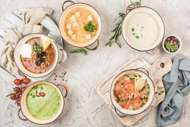 Plusieurs assiettes de soupes de viande et de poisson servies par le chef à la lumière. vue d'en haut avec un espace copie. nourriture de restaurant. mise à plat