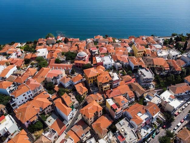 Plusieurs bâtiments aux toits orange, situés sur la côte de la mer égée