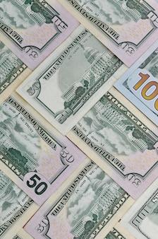 Plusieurs billets de cent cinquante dollars sur une surface de fond plat se bouchent. vue de dessus à plat