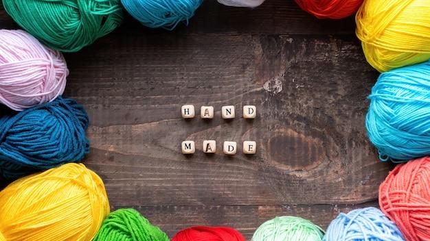Plusieurs boules colorées de fil avec des lettres en bois composant des mots faits à la main. vue de dessus