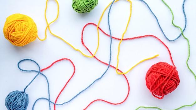 Plusieurs boules de fil partiellement non enroulées colorées sur un papier blanc. vue de dessus