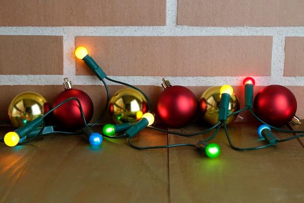 Plusieurs boules de noël et quelques lumières colorées sur une table en bois et un mur de briques avec espace de copie