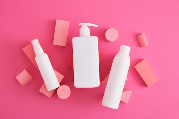 Plusieurs bouteilles de cosmétiques blanches différentes sur la composition de podiums géométriques, représentent la présentation du produit sur fond rose. vue de dessus