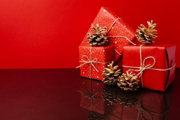 Plusieurs cadeaux de noël empilés dans un emballage festif avec des cônes