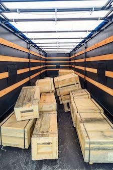 Plusieurs caisses en bois à l'intérieur de la semi-remorque cargo.