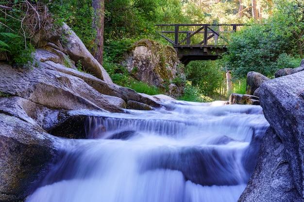 Plusieurs cascades passant sous un pont en bois. navacerrada.