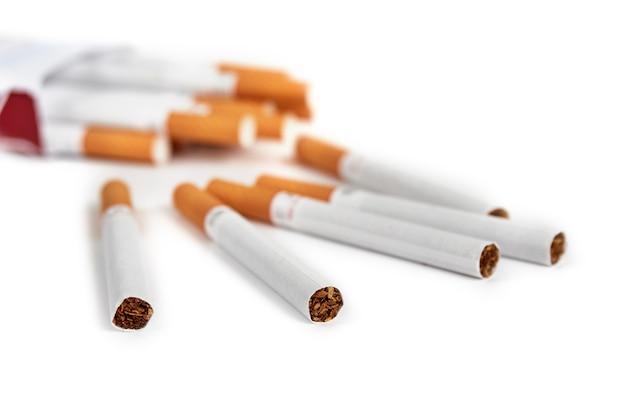 Plusieurs cigarettes à filtre dispersées sur une surface blanche isolée