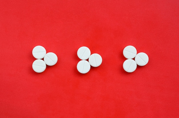 Plusieurs comprimés blancs se trouvent sur un fond rouge vif