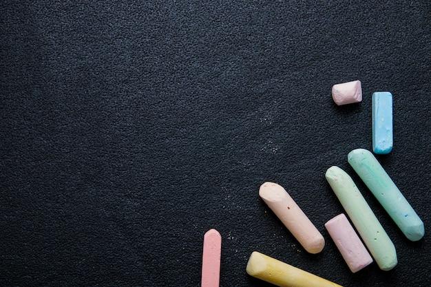 Plusieurs crayons de couleur sur fond noir, craie, dessiner sur l'asphalte avec de la craie, copie espace, vue du dessus