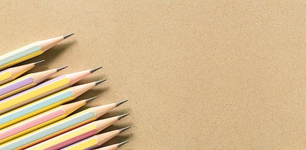 Plusieurs crayons sur papier brun vue sur un crayon brun en bois placé sur du papier brun pour le fond