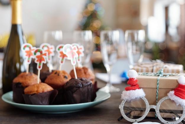 Plusieurs délicieux muffins faits maison avec de petites cartes de noël sur une assiette, une bouteille de champagne, des lunettes du père noël, des flûtes et des coffrets cadeaux sur la table