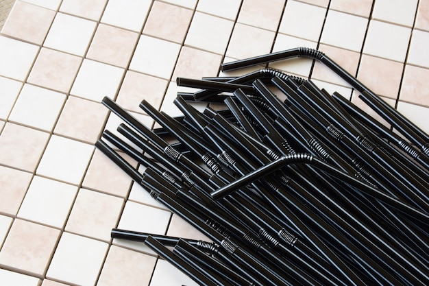Plusieurs dizaines de tubes noirs décoratifs pour cocktails sur fond de petite céramique