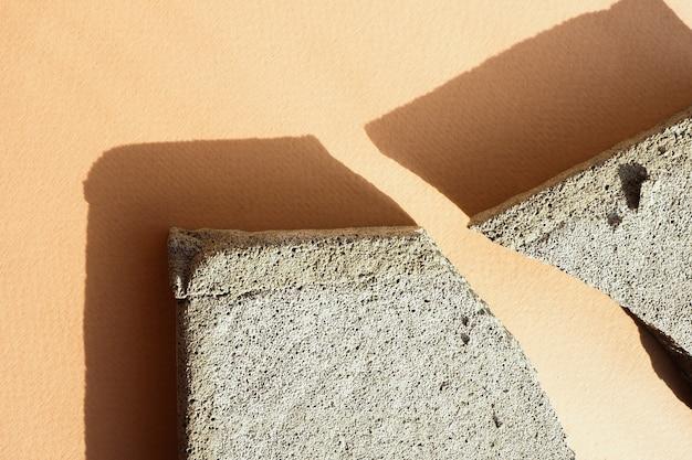 Plusieurs éclats de béton sur un fond de papier beige dans une lumière dure avec des ombres. mise en page à plat, vue de dessus.