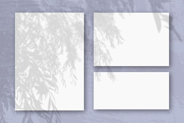 Plusieurs feuilles horizontales et verticales de papier texturé blanc sur fond de mur bleu