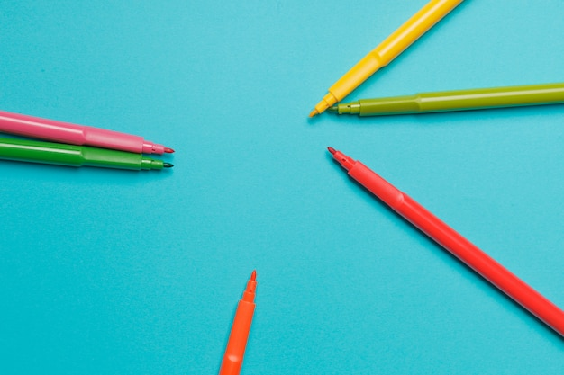 Plusieurs feutres de couleur sur papier bleu vif se bouchent