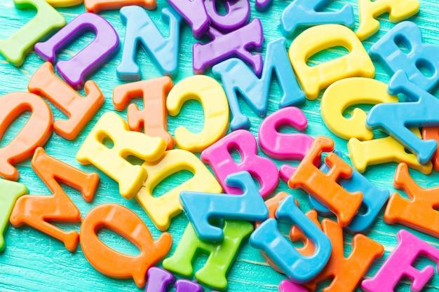 Plusieurs lettres colorées sur une table en bois