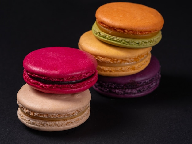 Plusieurs macarons colorés français sur un tableau noir. cuisinez à la maison.