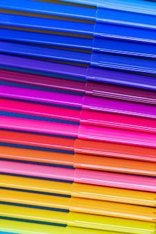 Plusieurs marqueurs multicolores brillants dans une rangée close-up.