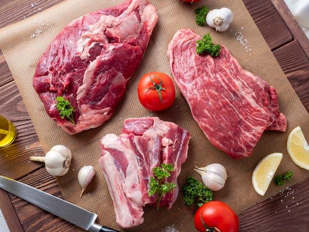 Plusieurs morceaux de bœuf angus noir marbré cru reposent sur du parchemin, entourés de verdure et de légumes. vue de dessus, pose à plat.