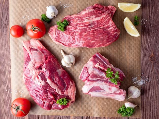 Plusieurs morceaux de bœuf black angus marbré cru reposent sur du parchemin entouré de verdure et de légumes. vue de dessus, mise à plat.