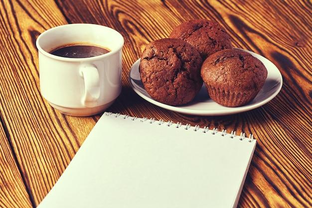 Plusieurs muffins au chocolat noir avec une tasse de café et un bloc-notes sur une table en bois.