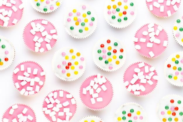 Plusieurs muffins colorés joliment décorés sur fond blanc, vue de dessus.