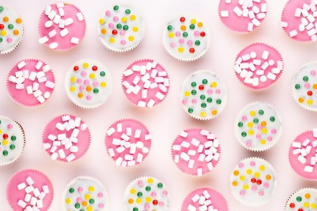 Plusieurs muffins colorés joliment décorés sur fond blanc, vue du dessus.