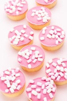 Plusieurs muffins colorés joliment décorés sur fond rose, vue de dessus.