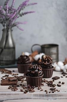 Plusieurs muffins ou cupcakes à la crème en forme de chocolat à table blanche. bougie festive brûle sur un gâteau au chocolat. il y a des pépites de chocolat dispersées à proximité
