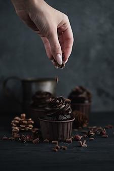 Plusieurs muffins ou cupcakes avec de la crème en forme de chocolat à table noire. bougie festive brûle sur un gâteau au chocolat. une main de femme émiette du chocolat râpé sur un gâteau