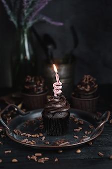 Plusieurs muffins ou cupcakes avec de la crème en forme de chocolat à table noire. bougie festive brûle sur un gâteau au chocolat.