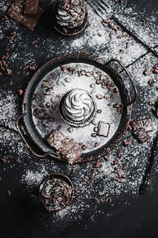 Plusieurs Muffins Ou Cupcakes Avec De La Crème En Forme De Chocolat à Table Noire. Du Sucre En Poudre Est Dispersé Sur Les Gâteaux. Vue De Dessus De Flatlay. Photo Premium