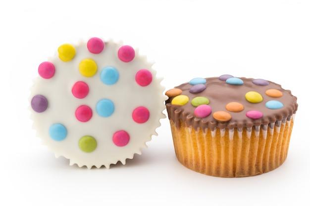 Plusieurs muffins décorés colorés sur blanc.