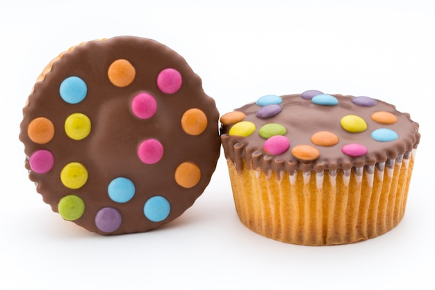 Plusieurs muffins décorés colorés sur fond blanc.
