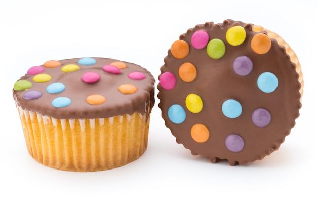 Plusieurs muffins décorés colorés sur une surface blanche.