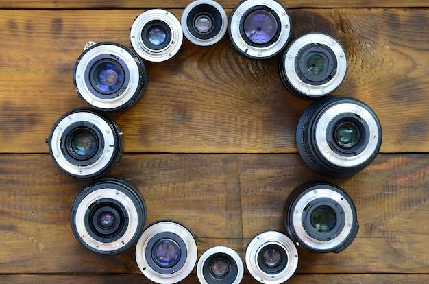 Plusieurs objectifs photographiques reposent sur une table en bois marron. espace pour le texte