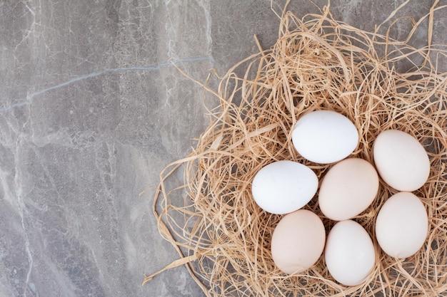 Plusieurs œufs frais blancs sur du foin sur fond de marbre. photo de haute qualité