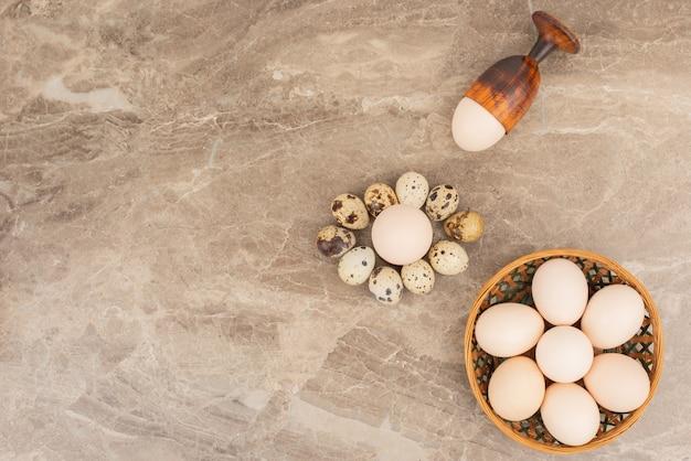 Plusieurs œufs sur le panier avec des œufs de caille dans la surface en marbre