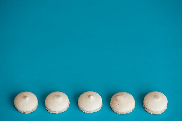 Plusieurs petits biscuits blancs disposés en rangée sur du bleu