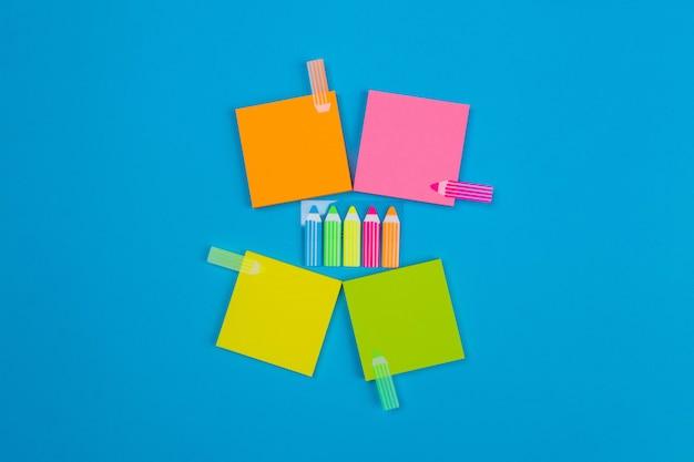 Plusieurs petits ensembles d'autocollants jaunes, oranges, roses, verts pliés en forme de carré disposés autour d'autocollants avec des crayons sur chaque autocollant en forme de crayons. place pour les notes.