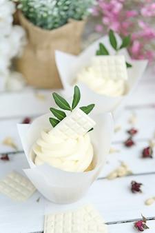 Plusieurs petits gâteaux et muffins à la crème au beurre blanc et une rose rose vif sur une table en bois blanche.
