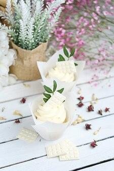 Plusieurs petits gâteaux et muffins à la crème au beurre blanc sur une table en bois blanc.