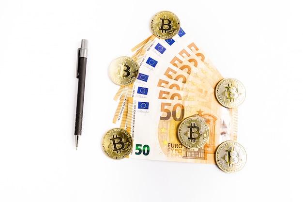 Plusieurs pièces d'or bitcoin à côté de billets en euros et d'un stylo