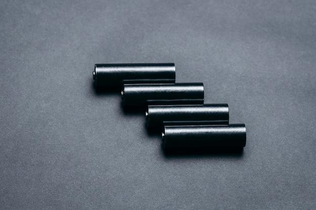 Plusieurs piles noires vierges aa sur espace papier noir