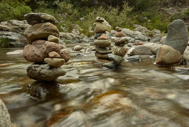 Plusieurs piles de roches interrompent l'écoulement de l'eau dans le ruisseau.