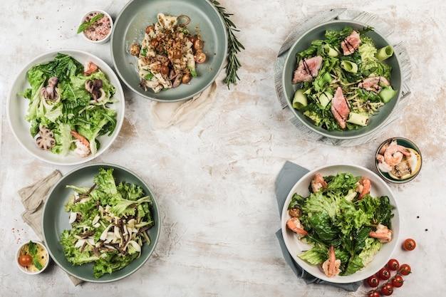 Plusieurs plats avec des salades de légumes frais avec du poisson et de la viande dans différents bols avec le flux du chef sur un fond clair, vue de dessus avec copyspace. pose à plat. nourriture de restaurant.