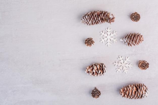 Plusieurs pommes de pin et flocons de neige sur une surface blanche